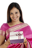 Smiling traditional woman holding a gift box — Stock Photo