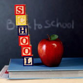 ABC cubes and red apple on text book — Stock Photo