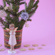 Angel figurine and fir branches on pink — Stock Photo #61627385