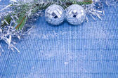 Two shiny disco balls on a fir branch covered with snow — Photo