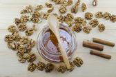 Jar of honey, wooden spoon and wallnuts — Stock Photo