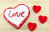 Heart shaped red candles and a box — Stock Photo