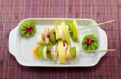Due spiedini completo con frutta colorata su un tavolo — Foto Stock