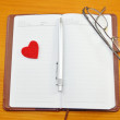Notebook, pencil and a small red heart on a table — Stock Photo #63942951