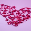 Heart made out of red Christmas tree pearls and stars — Stock Photo #63942995