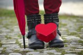 Heart shaped box standing on girl's boots — Stock Photo