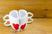 Heart shaped coffee mug on wooden background — Stock Photo