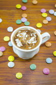 Cup of coffee and bombons of various colors — Stock Photo