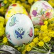 Hand painted decoupage Easter egg in a basket — Stock Photo #68941057