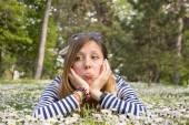 Sad brunette girl lying in the grass — Stock Photo