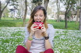 Brunette trying to eat her wallet in a park — Stock Photo
