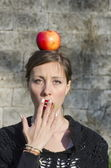 Shocked brunette with an apple on her head — Stock Photo