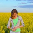 Brunette buttoning her shirt in a field of yellow flowers — Stock Photo #72494881