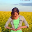 Brunette buttoning her shirt in a field of yellow flowers — Stock Photo #72494895