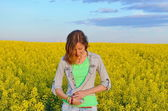 Brunette buttoning her shirt in a field of yellow flowers — Stock Photo