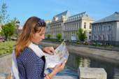 Young girl reading a map close to a river — Stock Photo