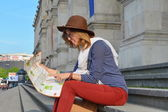 Young girl reading a map sitting on a staircase — Stock Photo