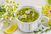 White porcelain cup filled with chamomile flowers — Stock Photo