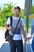 Young man entering a bus — Stock Photo