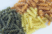 Tri-Color unprepared pasta stacked to form background — Stock Photo