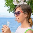 Brunette girl holding a white flower with seaside in background — Stock Photo #78799980