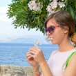 Brunette girl holding a white flower with seaside in background — Stock Photo #78801248
