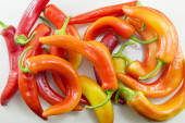 Fresh crooked orange and red peppers on a white wooden table — Stock Photo