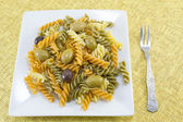 Colored macaroni with olives served on the yellow tablecloth wit — Stock Photo