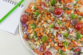 Ensalada de verduras en un plato junto a un cuaderno abierto y un lápiz para — Foto de Stock