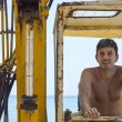 Young man sitting in a bulldozer at the beach — Stock Photo #79973188