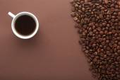 Hot coffee cup and beans on a brown background. — Stock Photo