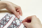 Hands girls embroider pattern cross. — Stock Photo