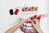 Woman embroiders national pattern red and black thread. — Stock Photo