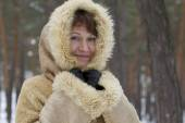 Girl with a smile envelop from the cold in warm sheepskin. — Stock Photo
