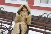 Portrait of emotional girl sitting on a bench in the winter. — Stockfoto