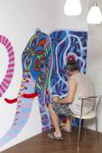 Painter paints with acrylic paints picture on the wall. — Foto Stock