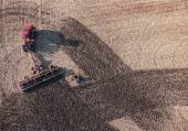 Aerial top view of tractor plowing a field — ストック写真