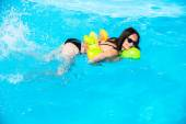 Girl swims in the pool on an inflatable circle — Stock Photo