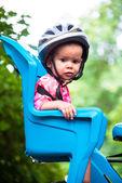 Küçük kız Bisiklet kask giymiş ve bisiklet koltukta oturur — Stok fotoğraf