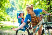 Mom on a bike with a small child, who wore a bicycle helmet and — Stock Photo