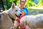 My mother with a small child playing with other people's dogs — Stock Photo
