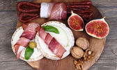Ham and sausage on a board on a wooden background. — Foto de Stock
