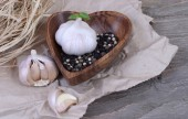 Garlic and pepper in wooden ware on a wooden background. — Stock Photo