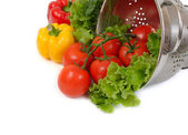 Fresh vegetables in a colander on a white background. — Stock Photo
