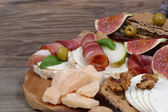Ham, smoked sausages and cheese on a wooden background. — Stock Photo
