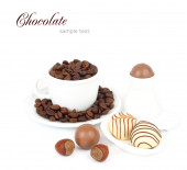 Cup with coffee grains and praline chocolate on a white background. — Stock Photo