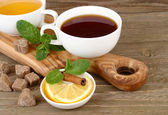 Two cups of black and green tea with a lemon, cinnamon and mint on a board on a wooden background. — Stock Photo