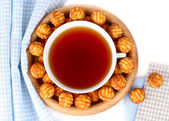 Cup of tea and biscuit cookies on a wooden plate on a white background. Top view. — Stock Photo