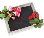 Cretaceous board (blackboard), roses and wooden heart on a white background. — Stock Photo