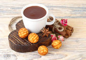 Cup of hot chocolate and biscuit cookies on wooden heart on a wooden background — Stock Photo